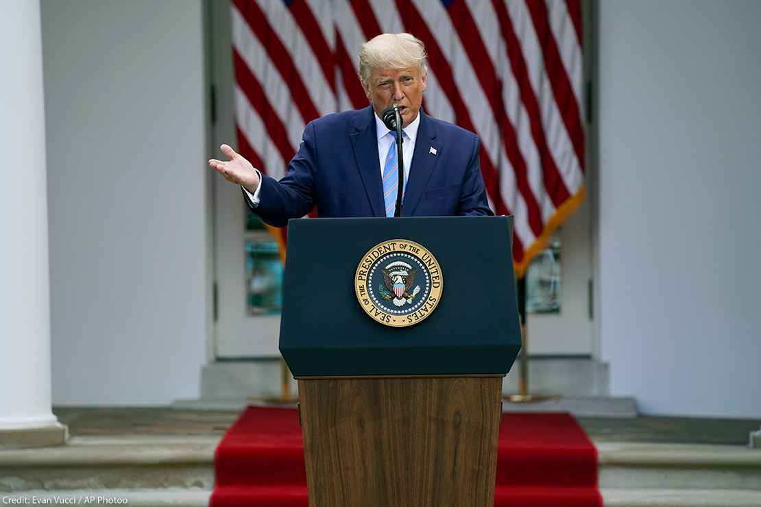President Donald Trump speaks about podium with presidential seal during an event in the Rose Garden of the White House.
