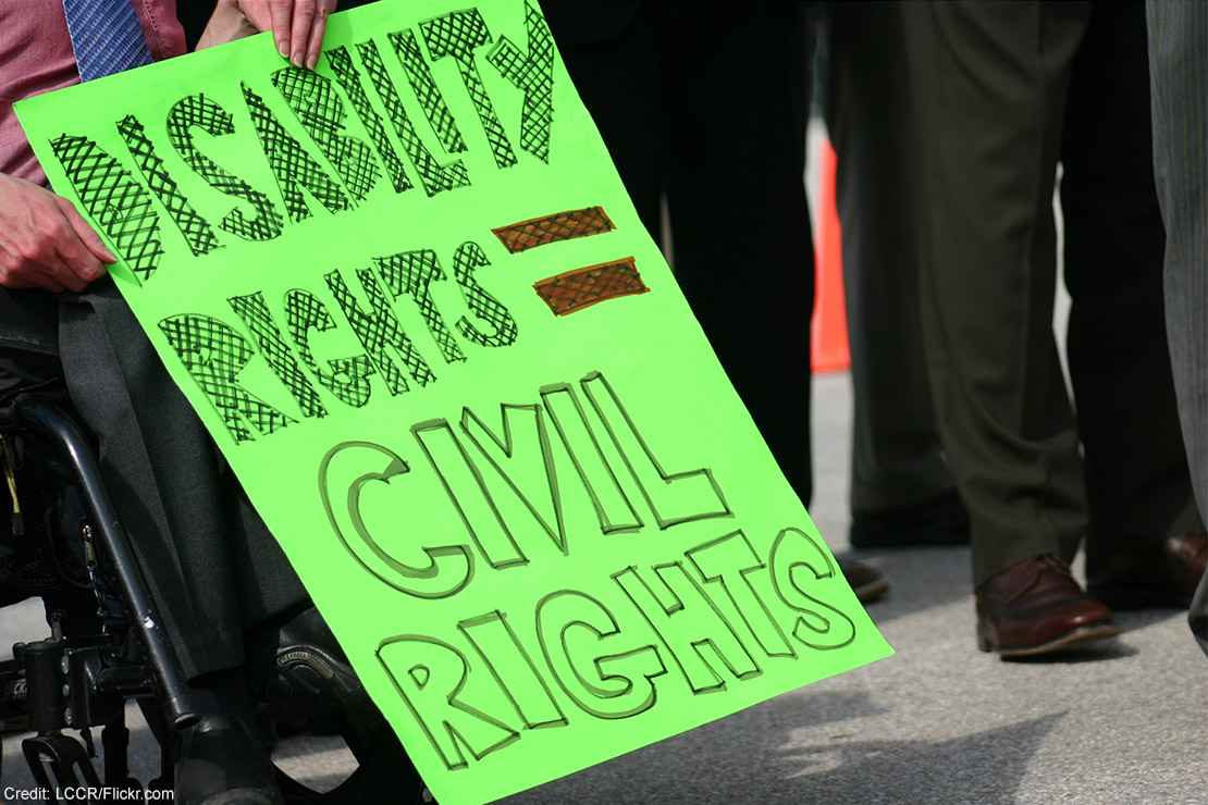"""A wheelchair user holding a sign with the text """"Disability rights = civil rights."""""""