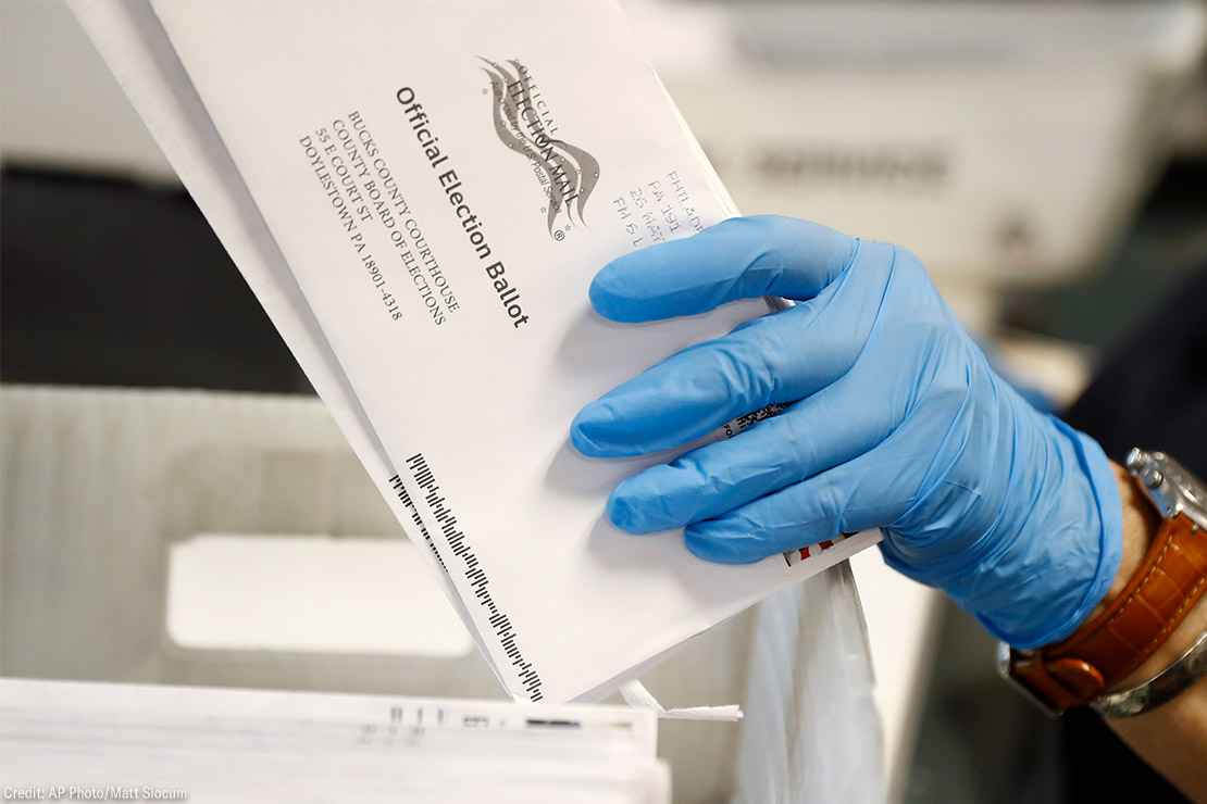 A worker processes mail-in ballots.