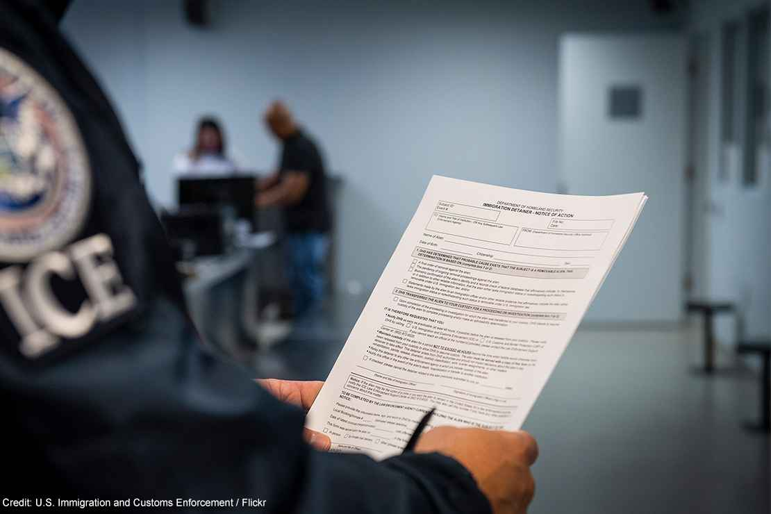 An ICE agent holding an Immigration Detainer form.