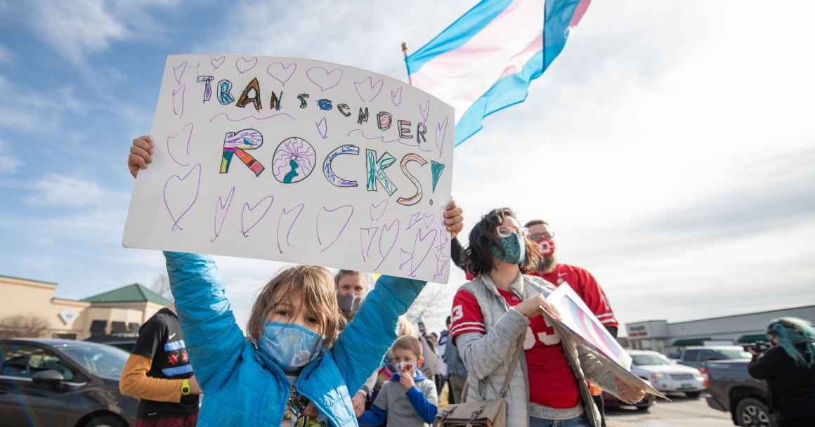 Kid with sign saying Transgender Rocks