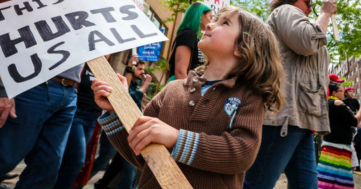 """""""This Law Hurts"""" sign held by a child"""